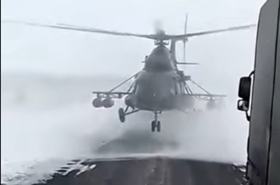 Helicóptero militar aterra na estrada para piloto pedir indicações