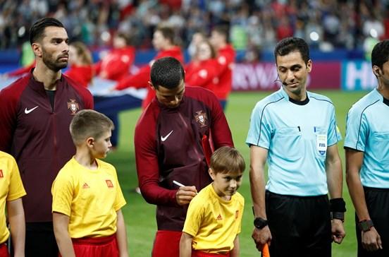 Ronaldo dá autógrafo a criança no relvado