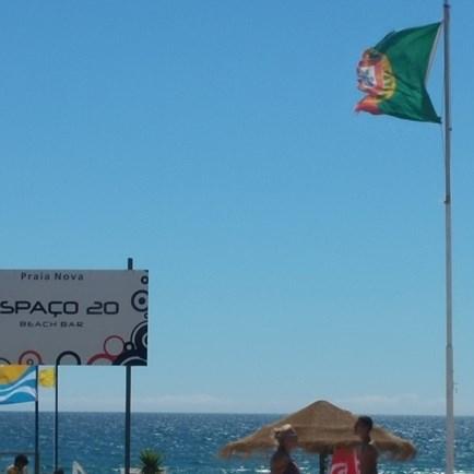 Bandeira de Portugal em mau estado em praia da Costa da Caparica