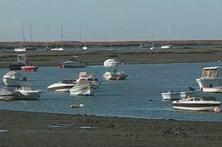 Barco vira na barra da praia de Faro com três pessoas a bordo