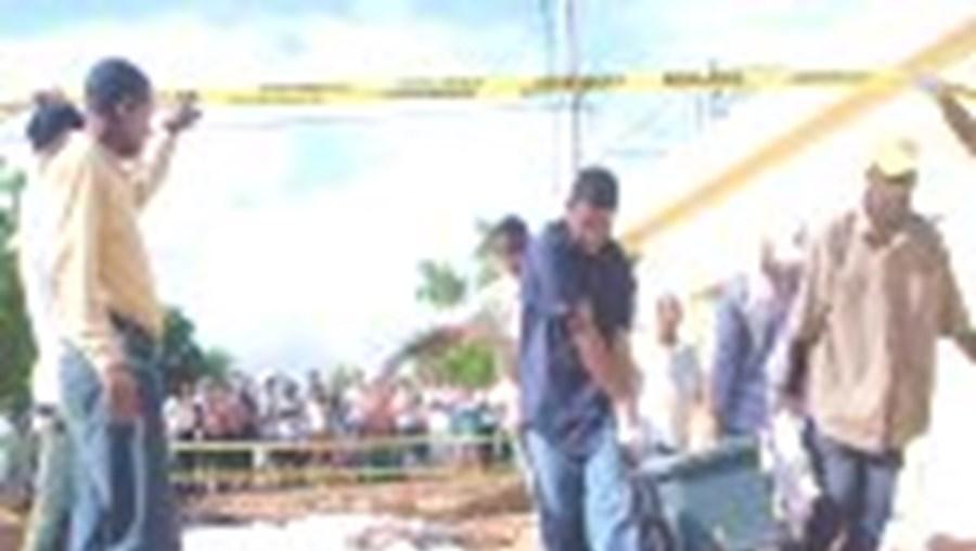 O corpo de uma vítima das cheias jaz à entrada de uma morgue na República Dominicana. Muitas pessoas acorrem às morgues em busca de corpos de entes queridos desaparecidos. Uma tragédia.