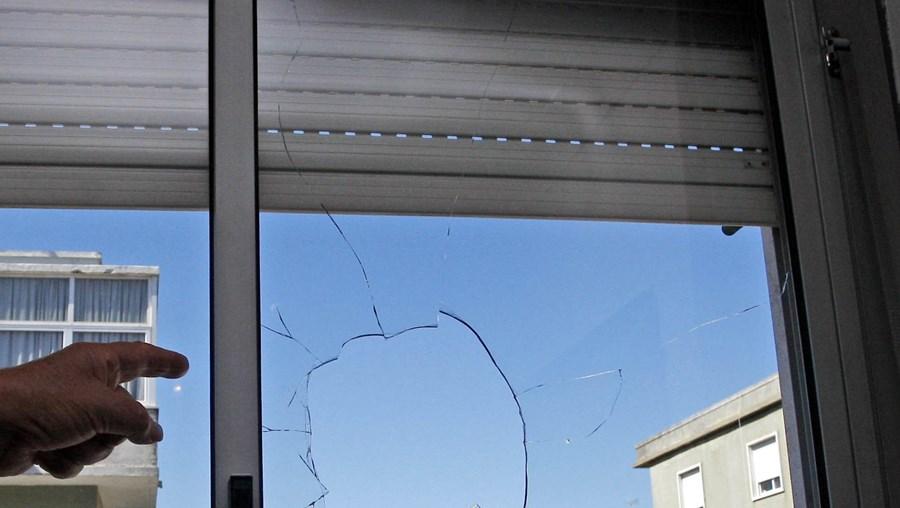 Moradora mostra ao CM janela partida por uma pedra