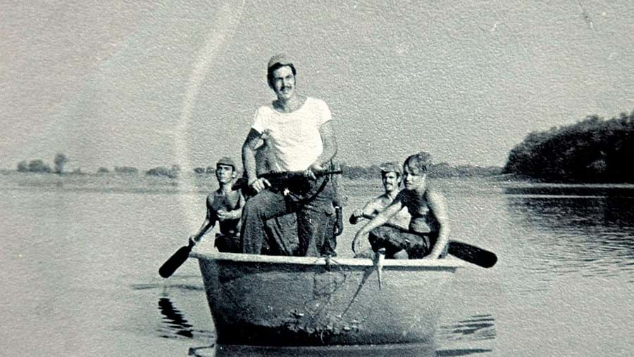 Mexia Alves em pé, num barco Sintex, com o qual se chegava ao destacamento de Mato Cão