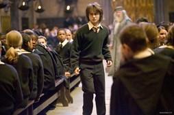 Harry Potter rodeadopelos colegas no Salão Nobre de Hogwarts, com o director da escola, Albus Dumbledore (Michael Gambon) ao fundo, em 'O Cálice de Fogo' (2005)