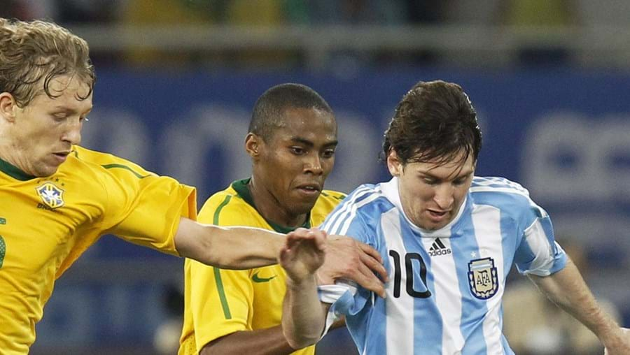 Os brasileiros Lucas (esq.) e Elias tentam travar o argentino Messi