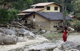 Habitante da cidade de Nova Friburgo assiste à subida do nível da água