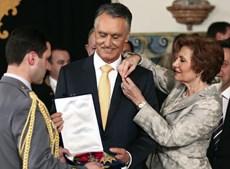 Na hora de receber as insígnias da Banda das Três Ordens, Maria Cavaco Silva compõe a gola do Presidente da República.