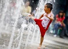 Criança chinesa diverte-se num repuxo em Pequim