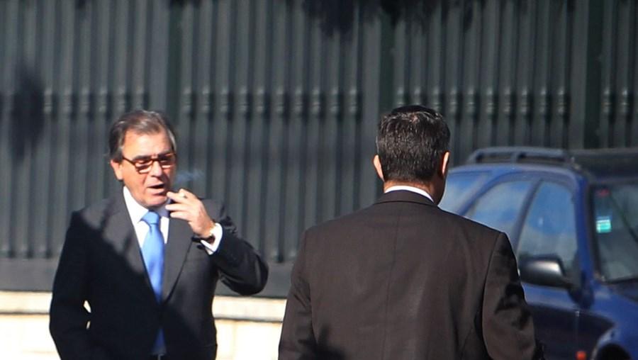 Dias Loureiro dá algumas instruções ao motorista antes da partida, enquanto se dirige para o automóvel de luxo à porta da mansão no Estoril