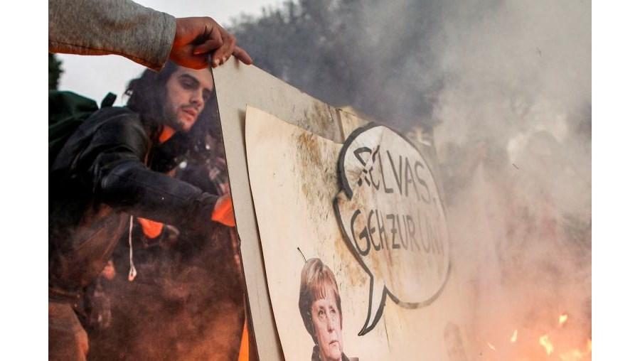 Fogueira feita com folhas de papel e imagens de Angela Merkel