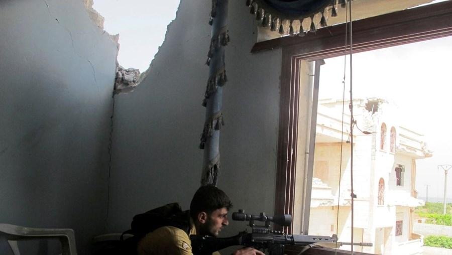 Um atirador furtivo do Exército Livre da Síria (rebeldes) em posição numa casa abandonada no distrito de Idlib, na Síria
