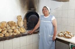 Emília David junto ao forno de onde sai o pão tradicional de Almeirim