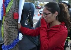 Krysha Converts chora enquanto lê mensagens escritas numa árvore durante um memorial não oficial em homenagem ao ator Paul Walker