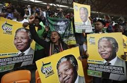 Pessoas seguram cartazes com imagem do antigo presidente da África do Sul, Nelson Madela