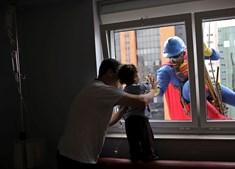 Homem mascarado de Super-Homem sorri para João Bertola, de dois anos, na companhia do seu pai. O menino era paciente no Hospital Infantil Sabará, em São Paulo, no Brasil