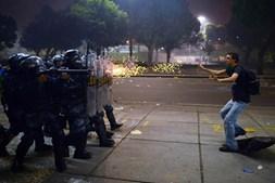 Manifestante alvejado com balas de borracha pela polícia de choque depois de confrontos durante protestos contra a corrupção e aumento dos preços, no Rio de Janeiro, Brasil
