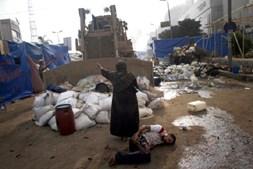 Mulher tenta impedir que uma escavadora militar esmague um ferido resultante dos confrontos entre forças de segurança e grupos da oposição, que causaram centenas de feridos no Cairo