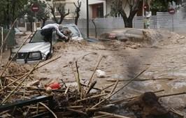 Homem salva mulher de dentro do seu carro numa estrada inundada em Chalandri, subúrbio de Atenas, em fevereiro