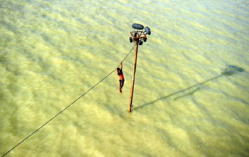Jovem indiano pendurado num cabo eléctrico antes de cair à água numa inundação do rio Ganges, em Allahabad, em agosto