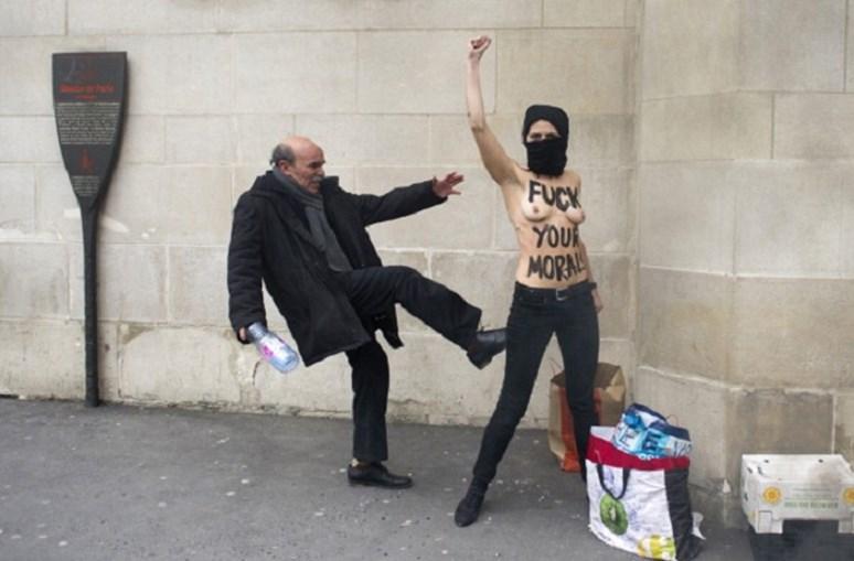 Homem pontapeia ativista ucraniana do movimento feminista 'Femen' enquanto ela, com os seios à mostra, ergue o punho a protestar contra os islâmicos, em frente à Grande Mesquita de Paris