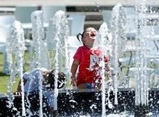 Crianças refrescam-se numa fonte durante o Open da Austrália 2014