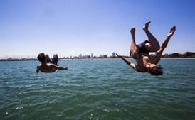 Pessoas mergulham no mar para combater calor