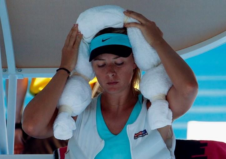 Tenista russa Maria Sharapova coloca uma toalha com gelo na cabeça, ao mesmo tempo que usa um colete de gelo, durante um intervalo de uma das suas partidas no Open da Austrália 2014
