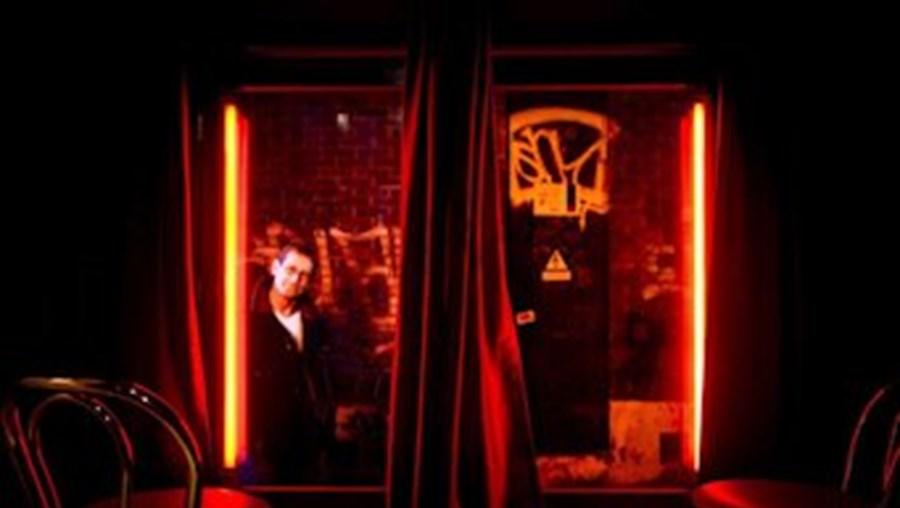 Um homem espreita para dentro de um bordel no Red Light District, em Amesterdão