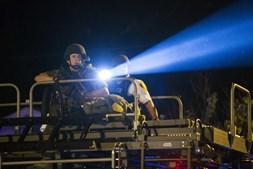 Agente da polícia aponta um foco de luz em cima do veículo blindado para um grupo de manifestantes em Missouri que contestam o comportamento policial que levou à morte de um adolescente negro