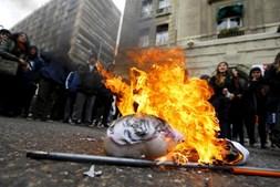 Alunos do ensino secundário queimam uma representação da presidente Michelle Bachelet num protesto que teve lugar em frente à Câmara Municipal de Santiago
