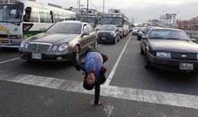 Renzo, de 11 anos, mostra as suas habilidades artísticas na rua, onde ganha a vida com as esmolas dos condutores