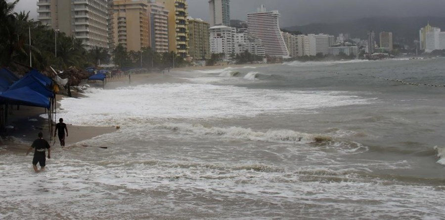 Homens a caminhar numa praia mexicana afetada por uma tempestade tropical