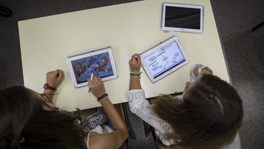Os alunos utilizam 'tablets' durante as aulas