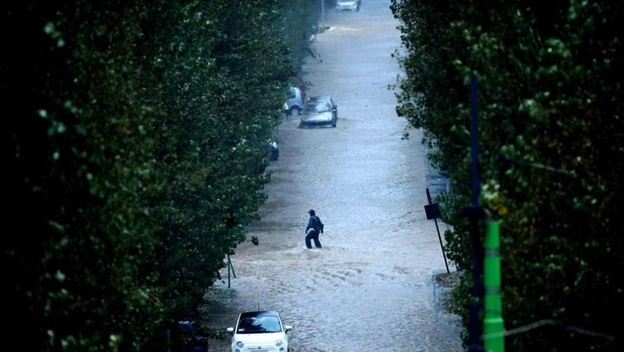 Pessoa anda numa rua inundada em Milão, após o rio Seveso ter transbordado