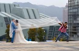Um casal chinês dá o primeiro beijo como marido e mulher enquanto um assistente fotográfico levanta o véu da noiva