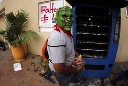 Um membro mascarado da CETEG (Coordenação Estatal de Professores de Guerrero), no México, vandaliza uma máquina de comida automática durante os protestos a exigir que o governo mexicano organize esforços para encontrar os 43 estudantes desaparecidos de Ayotzinapa