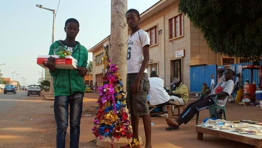 Ivo M'bai, à direita, e Ibraima Djaló, são dois vendedores que passam o dia a vender artigos de Natal