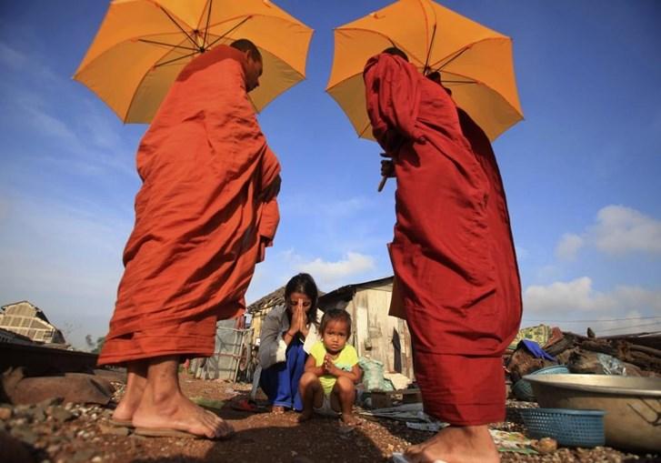 Uma mulher e a sua filha rezam após oferecerem esmolas a monges budistas em Phnom Penh, no Camboja