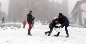 Crianças e adultos brincam com a neve