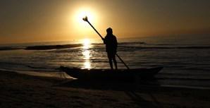 Palestiniano no seu barco, numa praia da cidade de Gaza, enquanto o Sol se põe