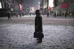 Homem parado no meio da rua durante queda de neve em Times Square, Nova Iorque
