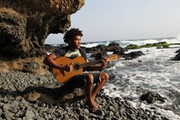 Tony de Marineta toca guitarra na praia, num momento mais descontraído