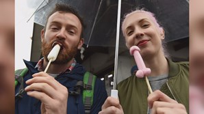 Dois turistas celebram o Festival Kanamara no Templo de Wakamiya Hachimangu, com doces em forma fálica