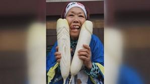 Mulher japonesa posa com dóis rábanos talhados para parcerem pénis, decorados com motivos fálicos e vaginais