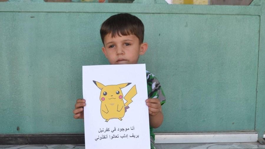 Menino sírio com um cartaz do Pokémon