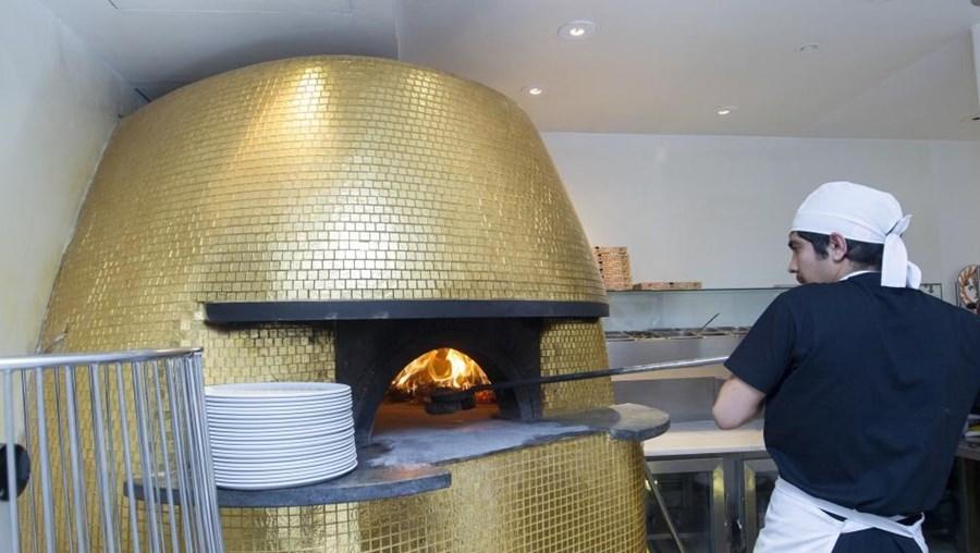 O forno é forrado com azulejos-pastilhas dourados que funciona a madeira de carvalho envelhecido