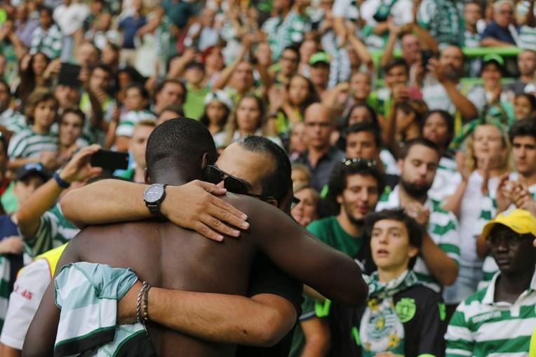 William Carvalho abraçado ao seu amigo e do adepto falecido. Deu-lhe a t-shirt do jogo para a família