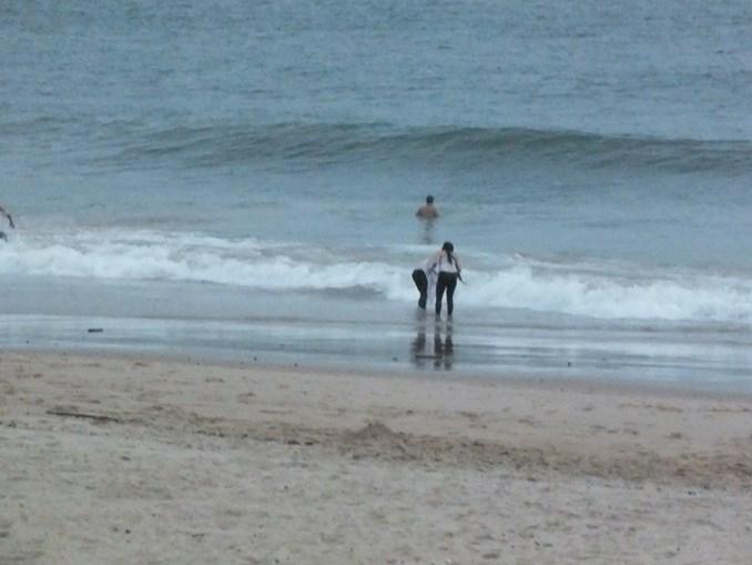 Três jovens  no mar. Durante  horas, iam buscar água em baldes ou simplesmente lavar roupas e o cabelo