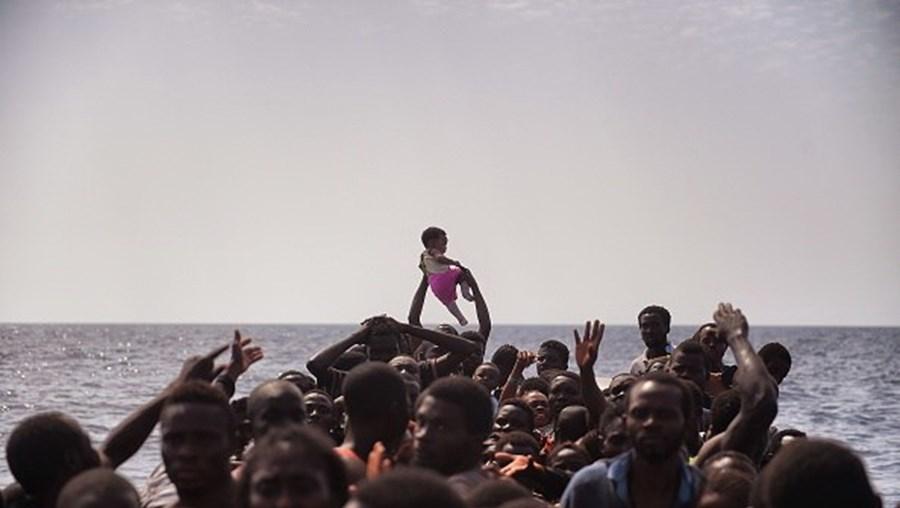 Um grupo de migrantes libaneses aguardam resgate junto ao mar Mediterrâneo