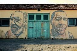 Retratos esculpidos de Vhils nas paredes dos velhos armazéns de Ponta Delgada